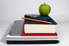 Laptop, books, calculator, pencil and apple. Laptop, books, pencil, calculator and appple on white background Royalty Free Stock Image