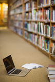 Laptop and books on the floor of library Stock Photography