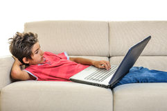 Laptop boy lying on the sofa Royalty Free Stock Images