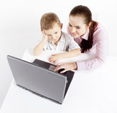 Laptop, boy and young woman. Boy and women sit at the laptop. He learns use the laptop. She shows him what to do Stock Photos