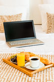 Laptop and breakfast tray in bed Royalty Free Stock Image