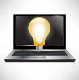 Laptop with bright light bulb Royalty Free Stock Photo