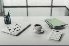 Laptop, Brillen und Tasse Kaffee mit Büroartikel Stockfotos