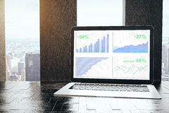 Laptop with business charts. On screen placed on windowsill workplace. Finance concept. 3D Rendering Stock Photography