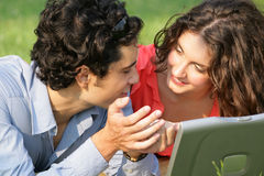 Laptop business couple. Young couple sitting on the park and working on a laptop Stock Image