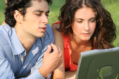 Laptop business couple. Young couple sitting on the park and working on a laptop Royalty Free Stock Photography