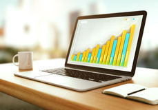 Laptop with business graph on a wooden table Stock Photos