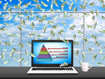 Laptop with business pyramid. On screen and flying 100 euro bills Stock Photo