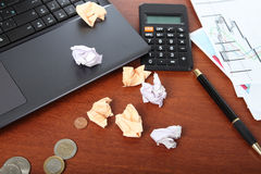 Laptop, calculator, cup of coffee and crumpled paper Stock Images