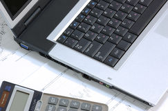 Laptop and calculator on finance charts. Laptop and calculator laying on finance charts Royalty Free Stock Photography