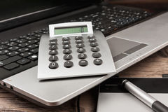 Laptop with a calculator and a graphic tablet on a wooden table. Royalty Free Stock Image