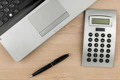 Laptop, calculator and pen on wooden table. Overhead view of working desk. Royalty Free Stock Photos