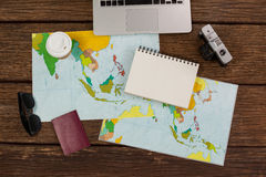 Laptop, camera, notepad, maps, passport and wayfarer. On wooden plank Stock Images