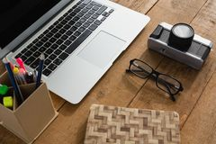 Laptop, camera, spectacles, notepad and pencil holder on wooden plank Royalty Free Stock Images
