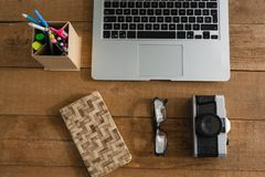 Laptop, camera, spectacles, notepad and pencil holder on wooden plank Royalty Free Stock Image