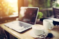 Laptop and cappuccino in the coffee shop stock image