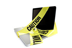 Laptop with caution tape around it. Laptop computer with caution tape wrapped around it Royalty Free Stock Images