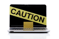 Laptop with caution tape and credit card. Laptop computer with yellow caution tape and gold credit card isolated on white background with reflection. horizontal Stock Photo