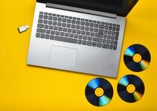 Laptop, CD-Laufwerk, USB-Blitz-Antrieb auf einem gelben Hintergrund Moderne und überholte digitale Medien Stockbild