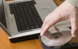 Laptop CDq. Mans hand placing a cd onto the tray of a laptop Royalty Free Stock Photography