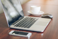 Laptop, cell phone, coffee cup on wood table background in office Stock Photography