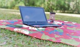 Laptop, celtelefoon en koffie op een picknickmat wordt geplaatst die vrijheid van bureau afschilderen en een natuurlijk aardburea stock afbeeldingen