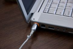 Laptop charging. Laptop plugged in and charging. Shallow DOF, focus on orange light royalty free stock photo