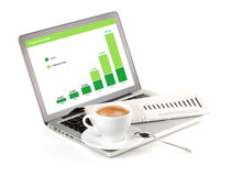 Laptop with chart, cappuchino cup and newspaper Royalty Free Stock Images