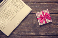 Laptop and chirstmas gift. On wooden table Royalty Free Stock Image