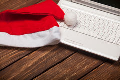 Laptop and chirstmas hat. On a wooden table Royalty Free Stock Photo