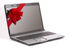 Laptop Christmas Gift. Laptop computer wrapped with red ribbon as a gift for Christmas. White background Royalty Free Stock Photography