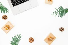 Laptop with Christmas gift boxes and pine cones on white background. New year holiday office composition. Top view. Flat lay Stock Images
