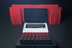 Laptop cinema front. Front view of abstract movie theater with laptop as screen, curtains and seats. Creativity and advertisement concept. Mock up, 3D Rendering Royalty Free Stock Image