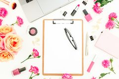 Laptop, clipboard, roses flowers, cosmetics and accessories on white background. Flat lay. Top view. Freelancer office or blogger. Laptop, clipboard, roses Royalty Free Stock Photos