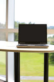 Laptop with clipping path in modern office. A modern laptop sits on a clean table. There is a clipping path on the laptop so you can ad a custom website into Stock Photo