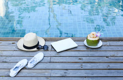 Laptop and coconut drink by awimming pool stock photography