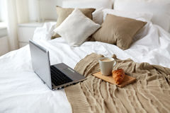 Laptop, coffee and croissant on bed at cozy home Stock Photography