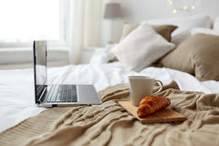 Laptop, coffee and croissant on bed at cozy home Stock Photo