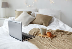 Laptop, coffee and croissant on bed at cozy home Stock Photos