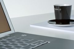 Laptop and coffee cup. Laptop and brown espresso cup on a pile of papers. White table top Stock Photography