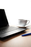 Laptop, coffee cup and blue pen Royalty Free Stock Photography
