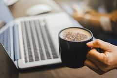 Young woman working on laptop and Holding coffee cup while sitting at his working place in Cafe. Laptop and coffee cup at his working place in Cafe. Enjoy royalty free stock photos