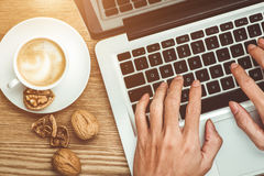 Laptop and coffee cup in male hands on a wooden floor royalty free stock photos