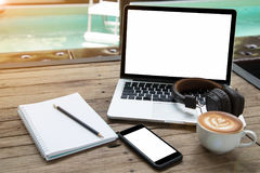 Laptop coffee cup notepad smartphone and headphone at poolside Royalty Free Stock Image