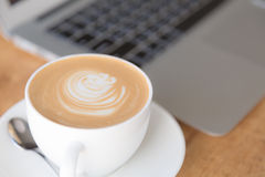 Laptop with coffee cup on old wooden table Royalty Free Stock Photo