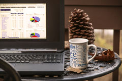 Laptop and coffee mug on outside table Stock Photo