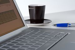 Laptop, coffee and pen Stock Photos