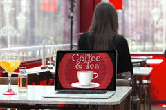 Laptop in a coffee shop with coffee menu on the screen and a cus Royalty Free Stock Images