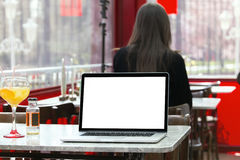 Laptop in a coffee shop with white screen and a customer in the Stock Photo