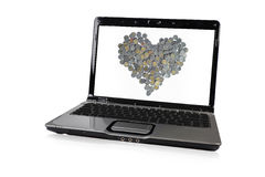Laptop with coins in heart screen Royalty Free Stock Image